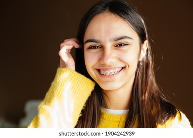 Portrait of a happy teen girl with braces and some acne smiling at home with the sun coming through the window