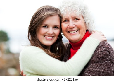 A portrait of a happy teen  granddaughter with her grandmother