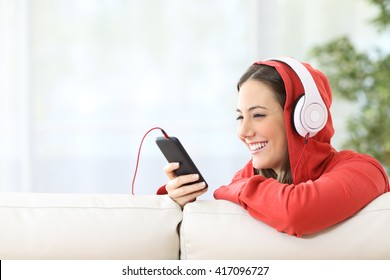Portrait of a happy teen listening music on line from smart phone sitting in a couch at home with white curtains in the background
