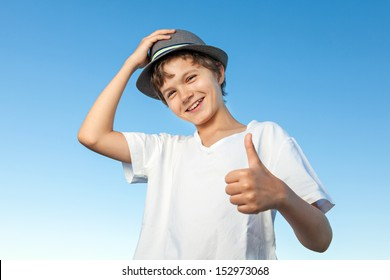 A portrait of a happy teenage boy outside, wearing a white shirt and hat against a blue sky, one hand is up at the hat, he is looking straight into the camera. he is giving a thumbs up sign.