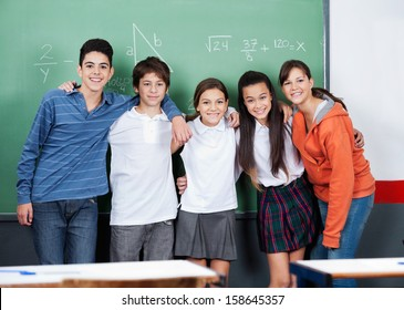 Portrait of happy teenage friends standing together against board in classroom