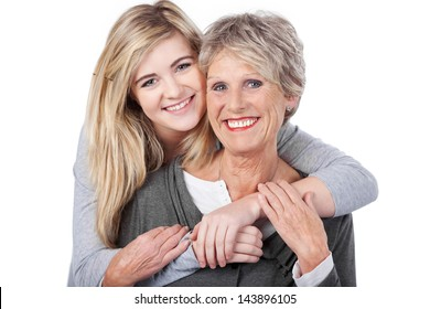 Portrait of a happy teenage girl embracing grandmother from behind against white background