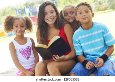 Portrait of happy teenage girl holding Holy Bible with siblings on park bench. Horizontal shot.