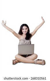 Portrait of happy teenage girl sitting on the floor while using a laptop and raise hands, isolated over white