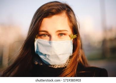 Retrato de una adolescente feliz con cara protectora y mascarilla médica parada afuera en la calle de la ciudad