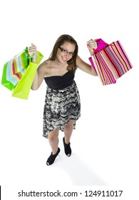 Portrait of a happy teenage girls holding up shopping bags against white background.