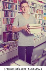 Portrait of happy teenager boy with book pile in shop