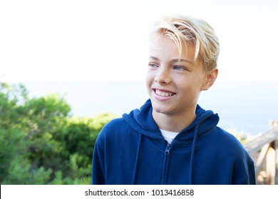 Portrait of a happy teenager boy with joyful expression by sea on sunny vacation, nature outdoors. Young male tourist visiting coastal destination, smiling and relaxing, leisure recreation lifestyle.
