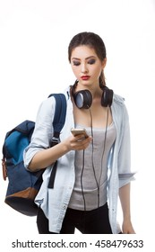 Portrait of happy teenager girl with school backpack and earphones smartphone isolated on white background. Happy woman in casual clothing. Good for sports and travel concept