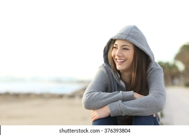Portrait of a happy teenager girl smiling and looking at side outside on the beach