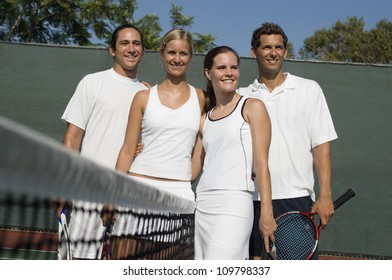 Portrait of happy tennis players standing by the net on tennis court
