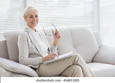 Portrait of happy therapist with notes sitting on sofa in office