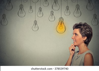Portrait happy thinking woman looking up with bright light idea bulb above head isolated on gray wall background