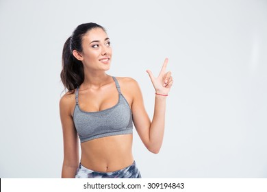 Portrait of a happy thoughtful girl pointing finger up isolated on a white background
