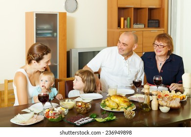 Portrait of happy  three generations family over dining table at home interior