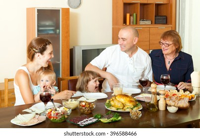 Portrait of happy three generations family posing together over celebratory table at home interior