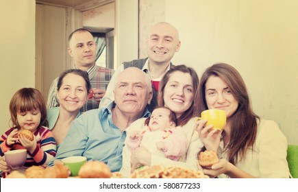 Portrait of happy three generations family communicate over tea at home