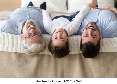 Portrait of happy three generations of men lying on bed upside down looking at camera smiling, little son, father and grandfather have fun enjoy leisure time together posing for picture at home