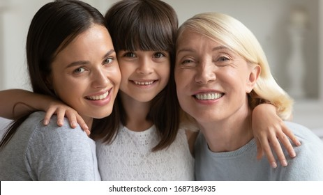 Portrait of happy three generations of women hug and cuddle posing at home together, smiling little preschooler girl embrace young mom and senior grandmother enjoy leisure family weekend