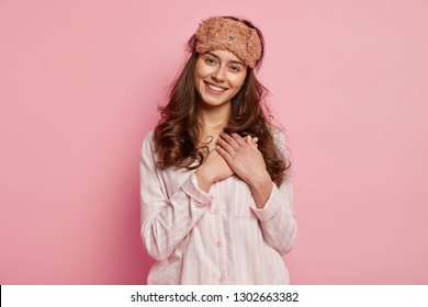 Portrait of happy touched woman recieves compliment from boyfried and breakfast in bed, keeps hand near heart to express her gratitude, wears casual domestic clothes and eyemask, smiles happily