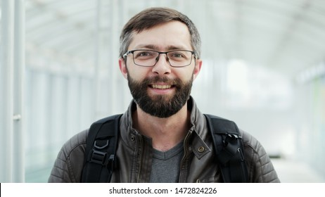 Portrait of happy tourist, bearded man smiling at the airport on white background, close-up