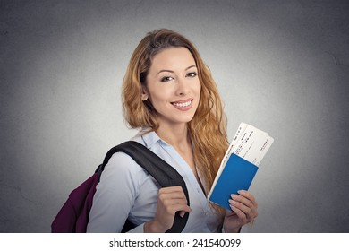 Portrait happy tourist young woman holding passport holiday flight ticket standing isolated on grey wall background. Positive human emotions face expression. Travel vacation getaway trip concept