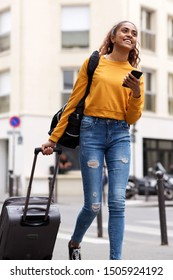 Portrait of happy travel woman walking with bags and mobile phone in city