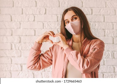 Portrait happy trendy hipster girl in pink medical face mask show heart shape symbol with hands. Young beautiful millennial woman in stylish protective face mask gesturing love peace sign with fingers
