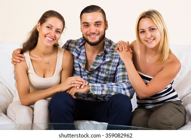 Portrait of happy two charming girls with young boyfriend