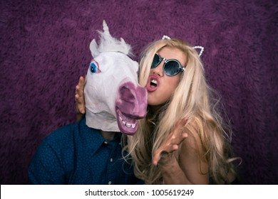 Portrait of happy unicorn in the arms of freaky young woman in sunglasses and kitty ears on the purple background. Expressive blond with strange guy. Unusual people shows emotions.