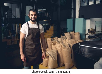 Portrait of happy unshaven master situating near full of beans sack at factory. Work concept