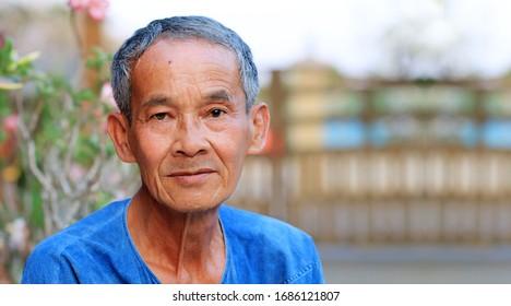 Portrait von glücklichem und ungelächlichem thailändischen Landsmann Senior Asian mit feinen Gesichtszügen, der Kamera anschaut, während er draußen vor seinem Haus im Garten steht. Ein Mann älter als 60 Jahre.