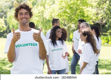 Portrait of happy volunteer gesturing thumbs up with friends disucssing in background