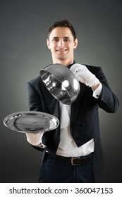 Portrait of happy waiter holding cloche over empty tray while standing against gray background