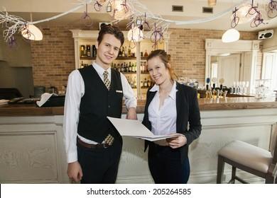 Portrait of happy waiter and waitress in restaurant