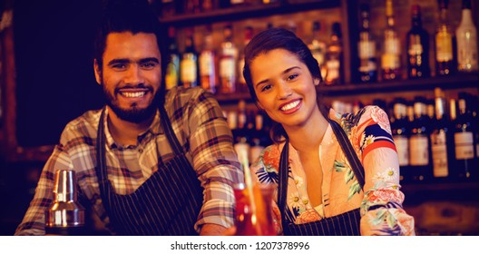 Portrait of happy waiter and waitress standing at counter in pub