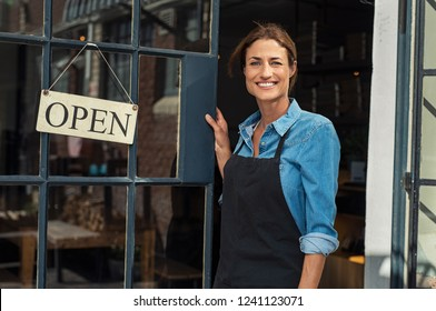 Portrait of a happy waitress standing at restaurant entrance. Portrait of mature business womanattend new customers in her coffee shop. Happy woman owner showing open sign in her small business shop.