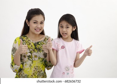 Portrait of happy white mother and young daughter with thumbs up - isolated. Happy family people concept