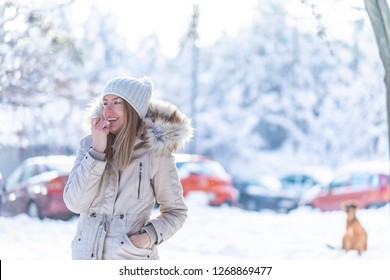 Portrait of a happy woman applying lip balm in winter with a snowy mountain in the background. Happy woman applying lip balm outdoors in winter in the snowy mountain
