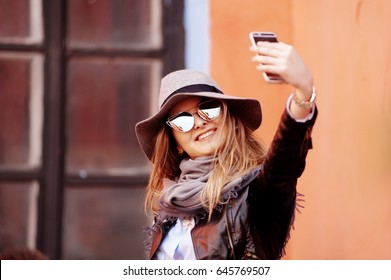 Portrait of a happy woman. Portrait of attractive young girl.Nice girl with sunglasses taking selfie. Woman wearing hat.