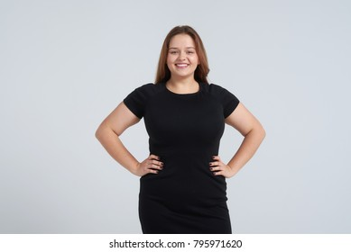 Portrait of happy woman in black dress posing at camera