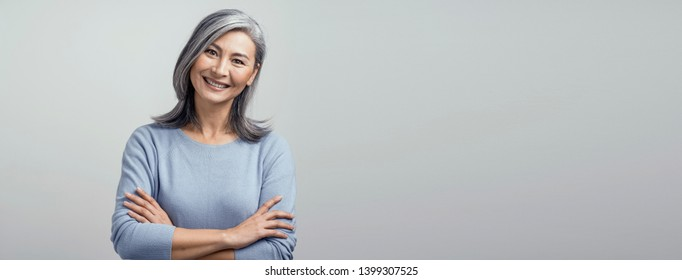 Portrait Of Happy Woman With Broad Smile And Crossed Arms. Cute Asian Grey-Haired Woman Broadly Smiles And Crossed Her Arms White Posing At Studio.