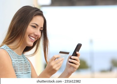 Portrait of a happy woman buying online with a smart phone outdoors