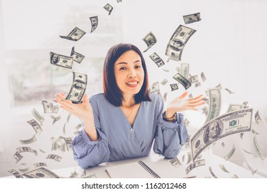 Portrait happy woman celebrates success under a money rain falling down dollar bills banknotes isolated on white wall background with copy spa