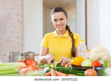 Portrait of  happy woman cooking  vegetarian salad at domestic kitchen