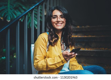 Portrait of happy woman dressed stylish using modern smartphone device outdoor chatting with friends social networks, positive student girl in hipster eyeglasses typing text message, Lifestyle People
