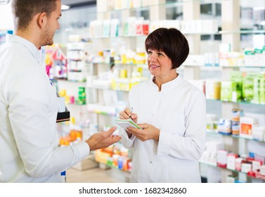 Portrait of happy woman druggist wearing white coat giving advice to customer in pharmacy. Focus on woman