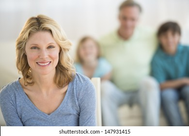 Portrait of happy woman with family sitting on sofa in background at home