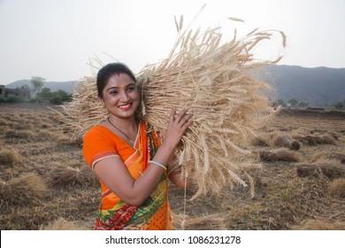 Portrait of Happy woman Farmer holding wheat