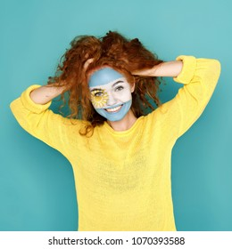 Portrait of happy woman with the flag of Argentina painted on her face. Football or soccer team fan, sport event, faceart and patriotism concept. Studio shot at blue background, copy space